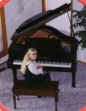 Erica sitting at her new baby grande piano.